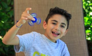 Young boy playing with a fidget spinner.