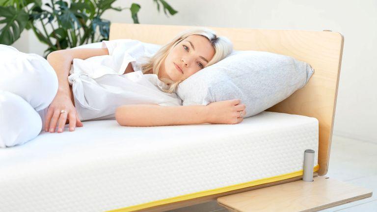 Best memory foam mattress: woman lying on eve mattress, wearing pajamas