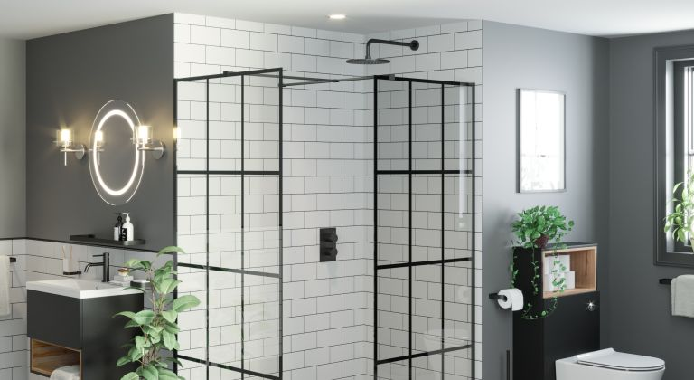 Black framed shower screen in a Crittall style with white metro tiles and matt black shower head