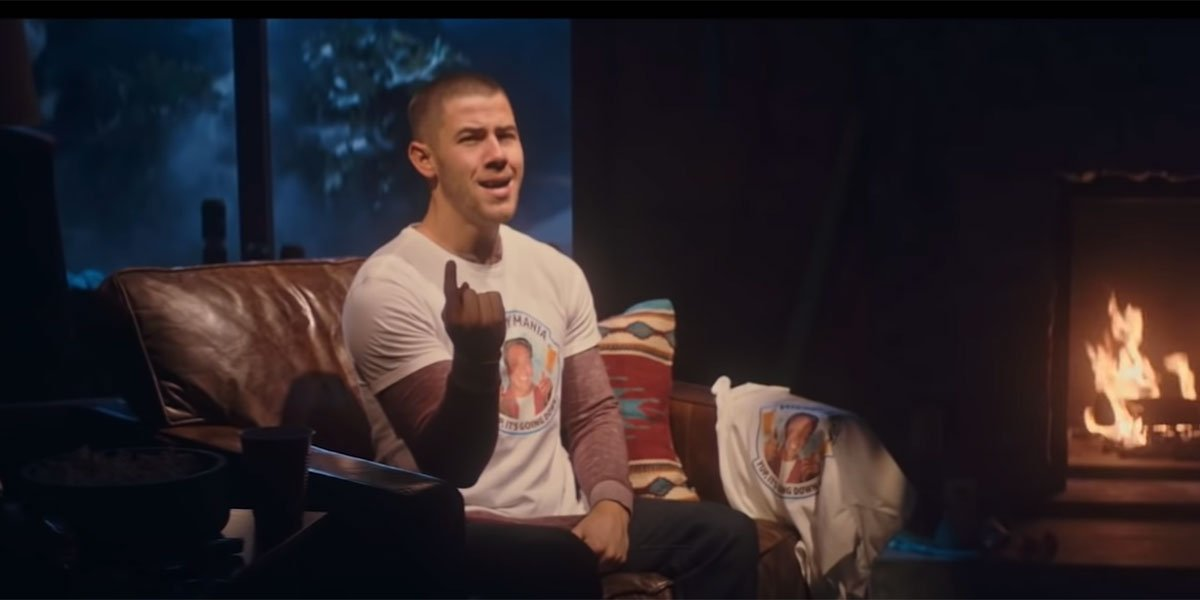 Nick Jonas singing by a fireplace on Saturday Night Live