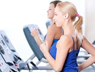 Two women run on treadmills.