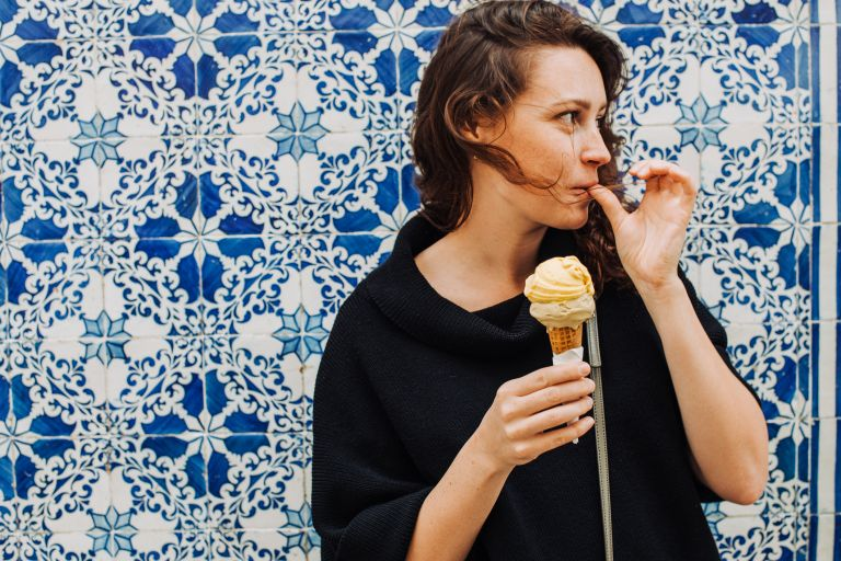 Millennial woman licking finger while eating ice cream at a tiled wall, destinations for solo travel