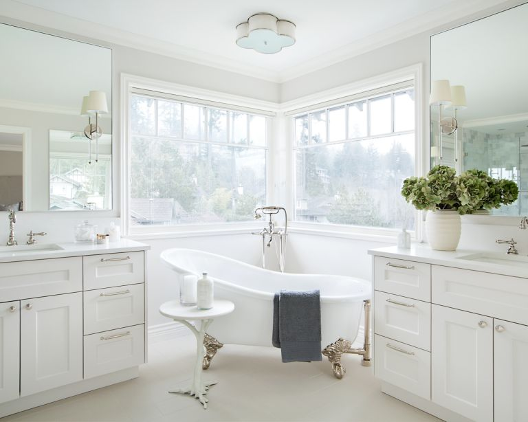 A white bathroom with a freestanding tub in front of a double corner window