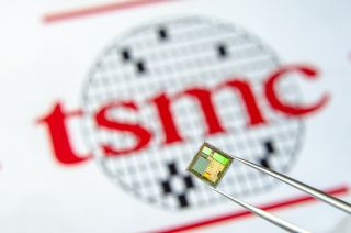 A chip being held in front of the TSMC logo.