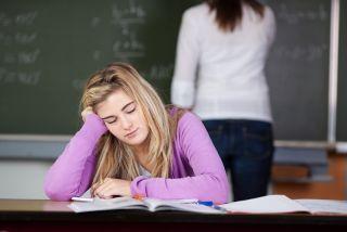 A teen girl dozes off in a classroom.