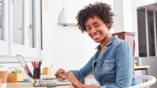Woman smiling at laptop with pencils next to her