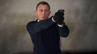 Daniel Craig as James Bond aiming a gun in No Time To Die