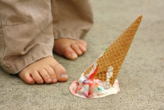 A child drops his ice cream cone on the ground.