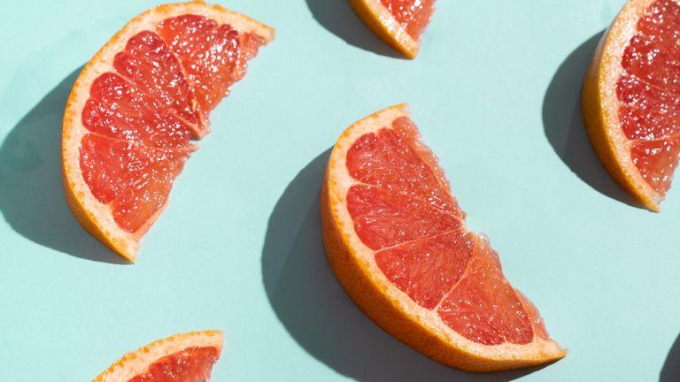 Grapefruit Slices On Turquoise Background - stock photo