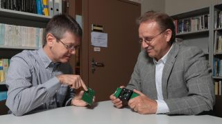 Scientists Edoardo Chabon and Claudio Brushini looking at a camera chip