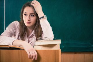 A teacher sits in her classroom looking exhausted