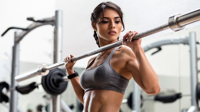 Woman with defined muscles lifting a barbell in the gym