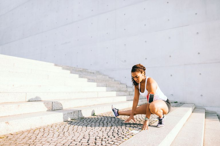 Woman outside an the bottom of steps in running gear crouching on the ground stretching