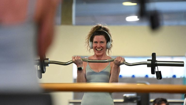 On the day the gyms reopen in England, a woman works out at Clissold Leisure Centre in London