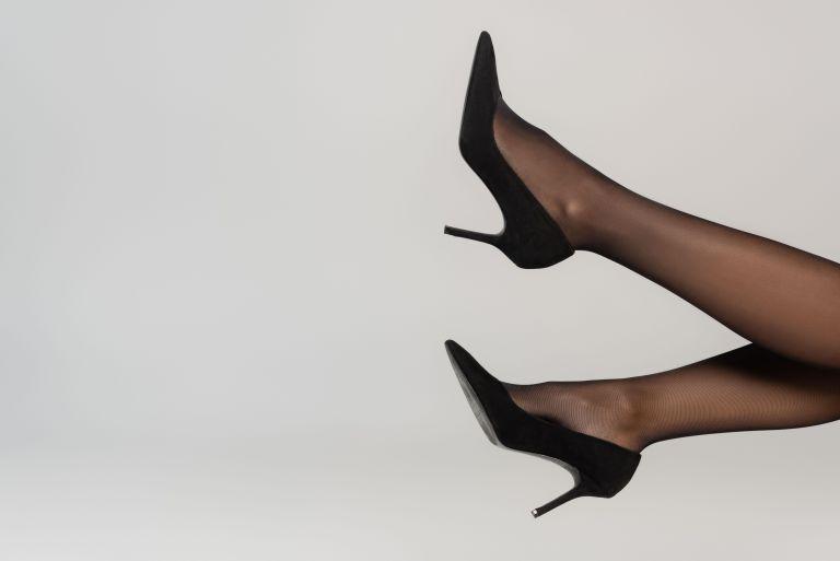 legs in black heels wearing black sheet tights against a pale grey background