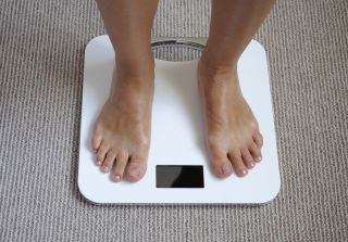A woman weighs herself on a bathroom scale.