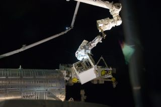 Fossum holds the Robotics Refueling Mission payload