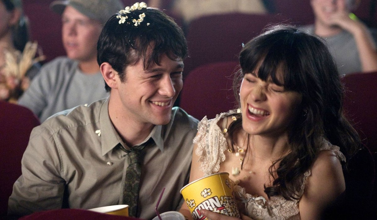 Joseph Gordon-Levitt and Zooey Deschanel laugh over popcorn at the movies in (500) Days of Summer.