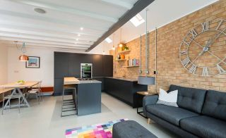 Contemporary open-plan kitchen, dining and living area with exposed brick wall