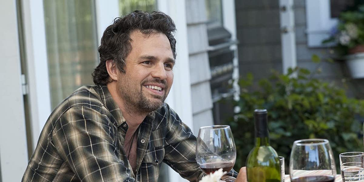 Paul (Mark Ruffalo) smiles while sitting at an outdoor table in 'The Kids Are All Right'