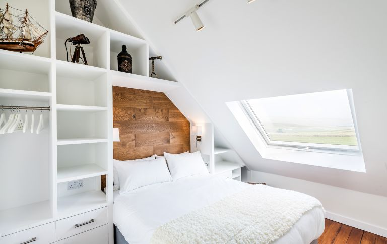 bed in a converted chapel with storage built around it