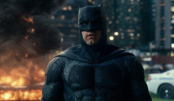 Justice League Batman standing at the Superman monument with a fire raging behind him