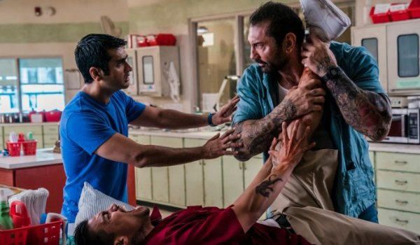 Stuber Kumail Nanjiani tries to calm Dave Bautista down, as he holds a bloody leg