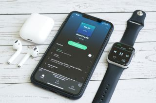 Composition of iPhone, Apple Watch and Airpods while using Spotify online music streaming apps. M
