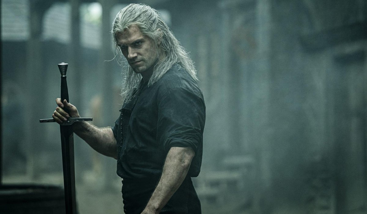 The Witcher Henry Cavill scowls while holding a sword upright