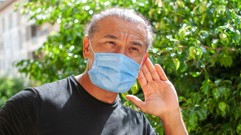Man struggling to hear whilst wearing a mask during the Covid-19 pandemic