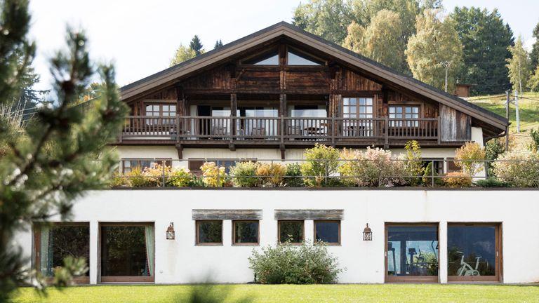 Balcony garden ideas featuring bushy plants along the balcony of a chalet-style dark wooden home.