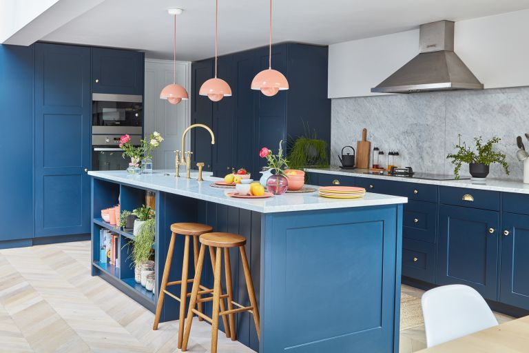 blue kitchen and island with marble countertop, parquet flooring, and three pink pendant lights over the island