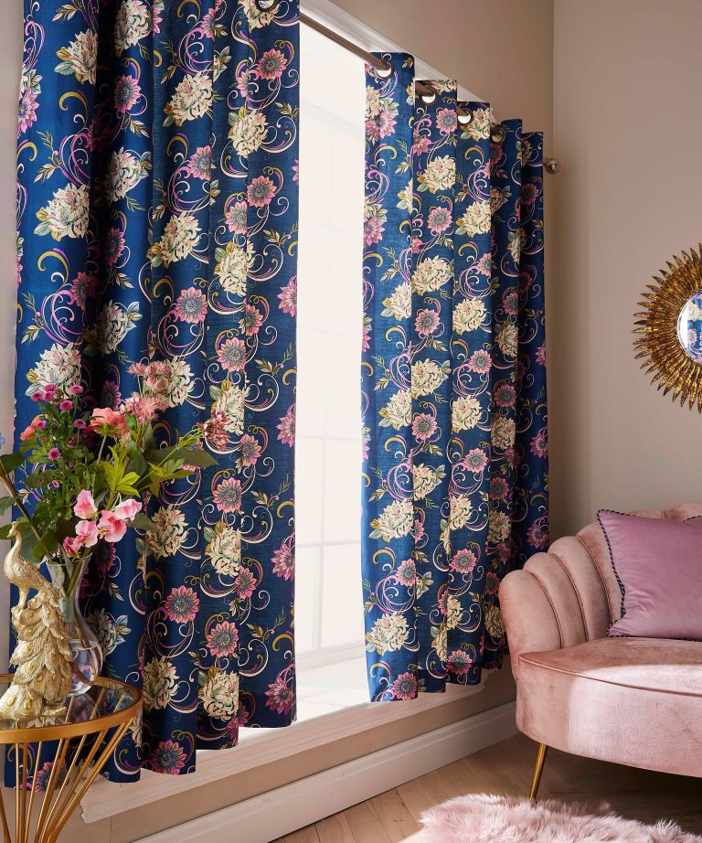 Blue and pink floral floor length curtains in living room with plush light pink velour armchair