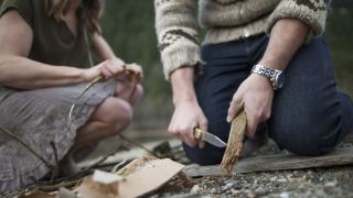 best camping knife: camping couple cutting wood