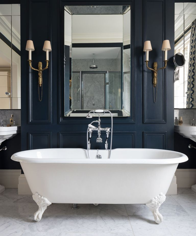 A photo from one of the best bathroom designers C.P. Hart showing a dark blue panelled bathroom with white bath and mirror.