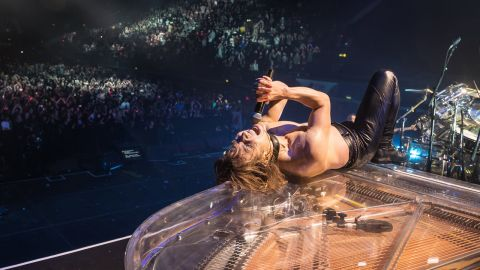 A photograph of Yoshiki lying on a piano