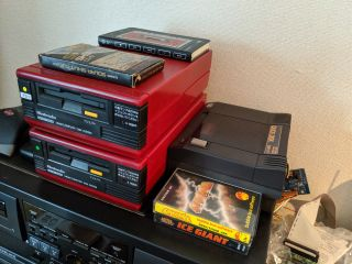 A pair of Famicom Disk Systems on the left, with the Quick Disk on the right.