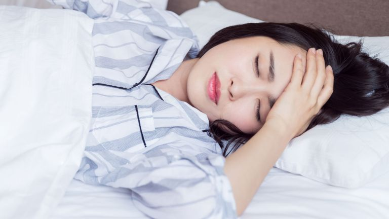 Woman in bed frowning, holding her head and suffering from sleep problems