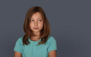A young girl with a doubtful look in a blue shirt.