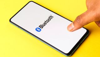 A thumb taps a generic smartphone with the Bluetooth logo and the word 'Bluetooth' displayed on the screen.