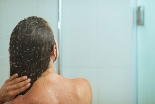 A woman stands in the shower.