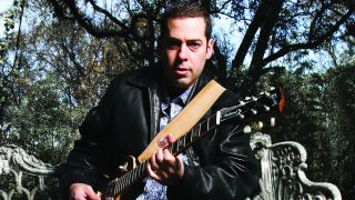 Albert Castiglia playing an electric guitar in a garden.
