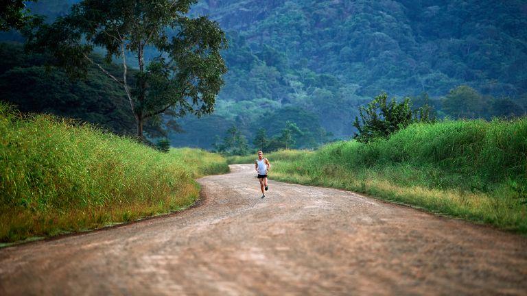 Man running in nature using a Garmin Forerunner watch