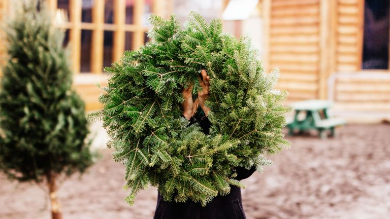 christmas wreath held by human by getty images