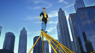 Superhero Invincible poses on top of a tall building