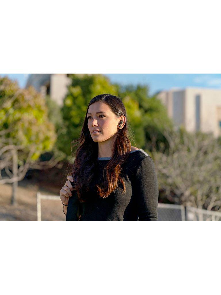 girl wearing wireless earphones outside in running clothes