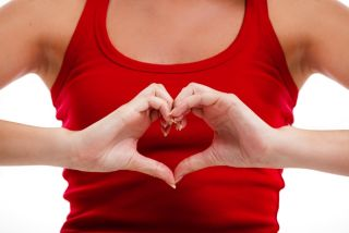 A woman holds her hands in a heart shape in front of her chest.