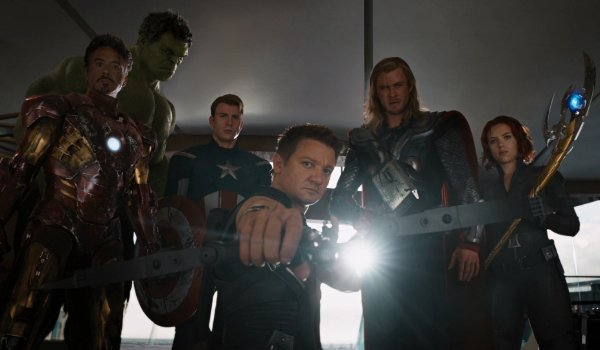 The Avengers standing in front of Loki, with Hawkeye aiming his bow and arrow at the camera