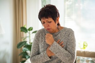 A stock photo of a woman coughing.