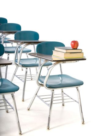 Empty classroom desk/chairs, one with books and apple.
